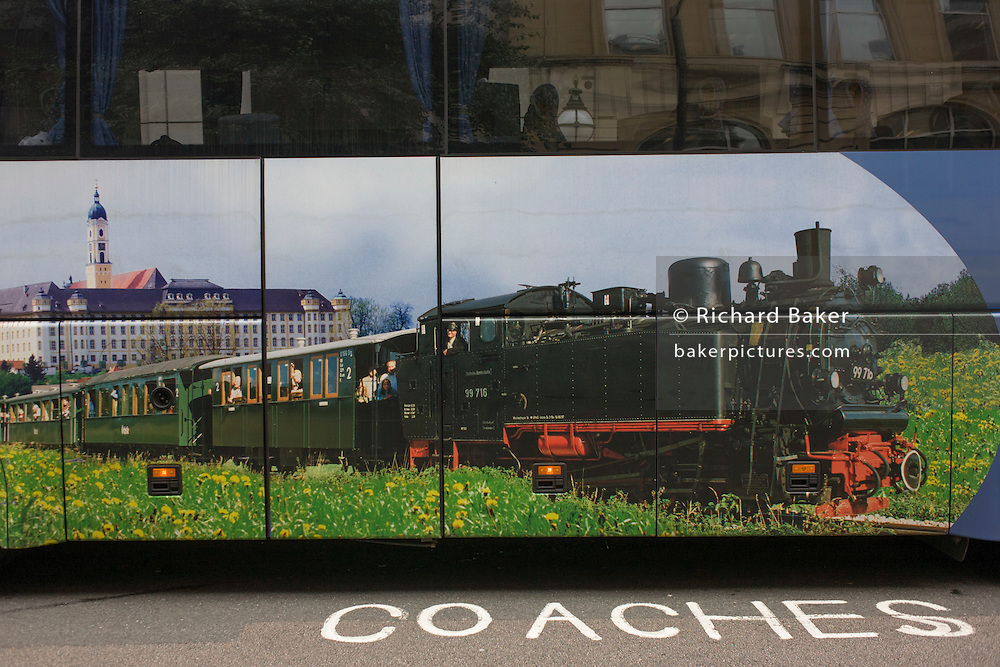 A tourist coach parked in central London shows an old steam train and carriages.