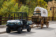 A modern vehicle pulls a covered wagon in Deadwood, Lawrence County, South Dakota, USA. After the discovery of large placer gold deposits in Deadwood Gulch in 1875, thousands of gold-seekers flocked to the new town of Deadwood from 1876 to 1879, leading to the Black Hills Gold Rush, despite the land being owned by the Sioux. At its height, the city had a population of 25,000, and attracted larger-than-life Old West figures including Wyatt Earp, Calamity Jane, and Wild Bill Hickok (who was killed there). The entire city is now designated as a National Historic Landmark District, for its well-preserved Gold Rush-era architecture.
