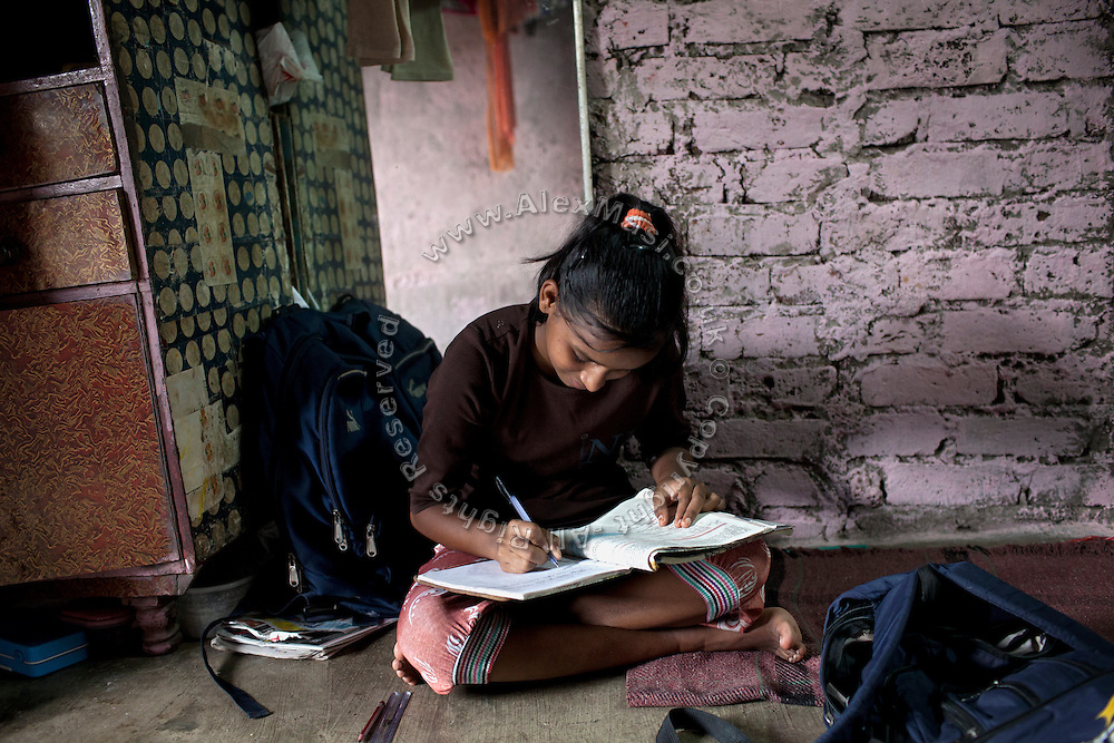 Mayuri Mahesh Pandit, 13, is completing her school homework before leaving to participate at the Unicef-run 'Deepshikha Prerika' project inside the Milind Nagar Pipeline Area, an urban slum on the outskirts of Mumbai, Maharashtra, India, where she resides with her family.