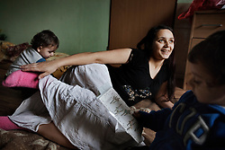 "Veronika Sindelárová plays with her children Rinaldo Gina, 2, and Fabián Gina, 1, and her half-sister in their home in Ostrava, Czech Republic on March 1, 2012. Veronika was one of 18 Roma children who were represented in the D.H. and Others v. Czech Republic case, the first challenge to systemic racial segregation in education to reach the European Court of Human Rights. When this case was first brought in 2000, Roma children in the Czech Republic were 27 times more likely to be placed in ""special schools,"" intended for the mentally disabled, than non-Roma children. In 2007, the Grand Chamber of the European Court of Human Rights ruled that this pattern of segregation violated nondiscrimination protections in the European Convention on Human Rights. Despite this landmark decision, little change has occurred: the ""special schools"" have been renamed but follow the same substandard curriculum and Roma continue to be assigned to these schools in disproportionate numbers. The process of integration has barely begun."