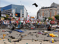 Milk farmers throw boots and clothes during a demonstration outside the European Council headquarters in Brussels July 12, 2010. Milk producers protested against lower selling prices of milk outside a meeting of European Union agriculture ministers. REUTERS/ Thierry Roge (BELGIUM - Tags: AGRICULTURE BUSINESS CIVIL UNREST POLITICS)