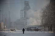 A man walk down a snow covered street as water vapor and smoke rise from a Tonghua Iron & Steel Group Co. plant in the distance in the Erdaojiang district in Tonghua, Jilin province, China, on Wednesday, Jan. 6, 2016. The citys once-vaunted state-run steel mills have slipped inexorably into decline, weighed down by slumping global markets, a changing economy, and the burden of costs and responsibilities to the people of the town they fostered. Previous attempts to privatise the enterprise have met with stiff resistance, one such attempt resulted the mob lynching and death of a private businessman who wanted to invest and streamline the operation.
