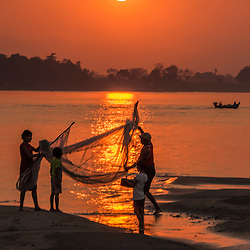 Sunset on the Irrawaddy river. This family are landing their fresh catch from today. <br /> <br /> During dry season, many villagers venture to the riverbanks to settle for some months, growing certain kinds of vegetables and fish for their daily needs. Myanmar agriculture is characterized by small-scale, subsistence, family farming / or fishing.
