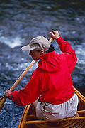 "A young woman in a bright red jacket paddles a vintage wooden canoe in a stream. MODEL RELEASED - To license this image, click on the shopping cart below - -- Determine pricing and license this image, simply by clicking ""Add To Cart"" below"