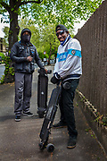 Two masked brothers staying fit in Hackney on their electric skateboards on 25th April 2020 in London, United Kingdom. Social distancing measures like this are steps taken to reduce social interaction between people to help reduce the transmission of coronavirus COVID-19. Sunbathing is banned during the crisis and the only time people should be outside is when taking exercise.