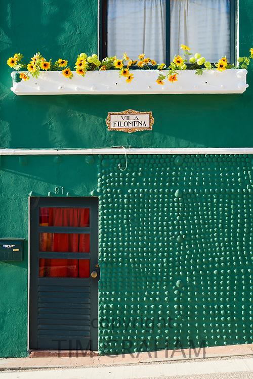 Bright painted house with stone textured wall in Costa Nova do Prado a village with many holiday homes near Aveiro,  Portugal