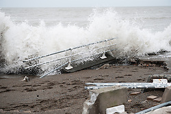 © London News Pictures. 05/01/2014. Aberystwyth, UK.  Strong waves continue to crash against the seafront at Aberystwyth promenade which is littered with debris following days of high tides and storms. Much of the seafront has been severely damaged by the pounding pif the waves, with the likely cost of repairs running into the millions of pounds. Photo credit Keith Morris: LNP