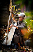 Harp player Sarajane Williams plays in her back yard in Macungie, Pa..<br /> - Photography by Donna Fisher<br /> - ©2020 - Donna Fisher Photography, LLC <br /> - donnafisherphoto.com