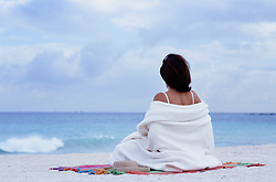 woman wrapped in a blanket sitting on the beach looking at the ocean in Florida