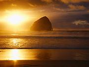 Sun setting beyond Haystack Rock at Cape Kiwanda, coast of Oregon.