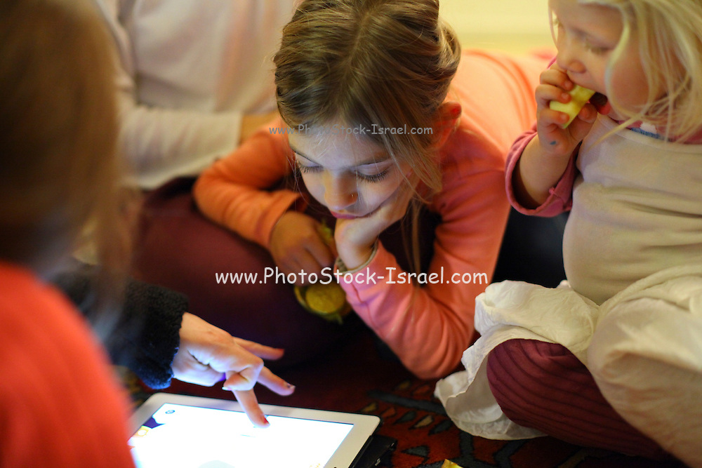 Family plays with an iPad in  living-room
