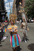 Two people wear elaborate costumes with very tall headdresses.