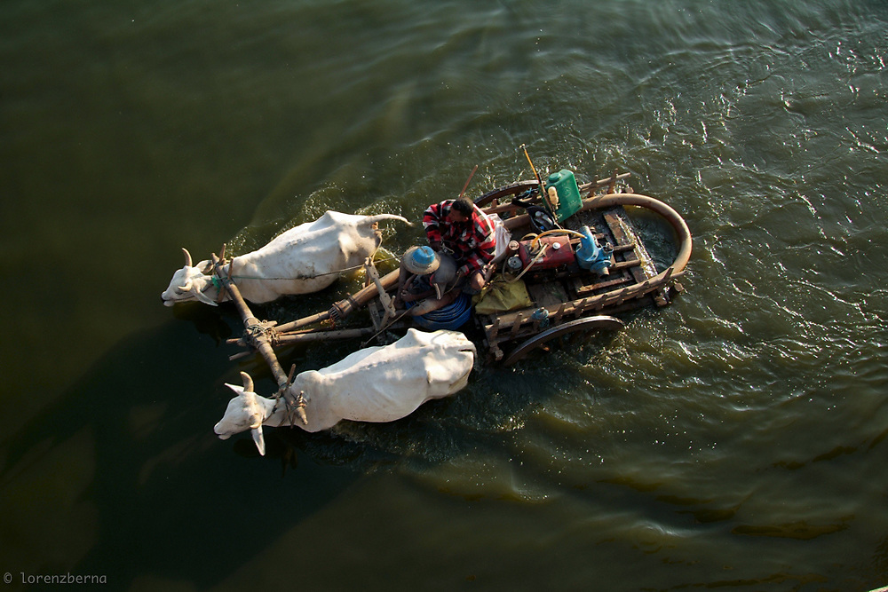 Two farmers on ox cart are crossing the Taungthaman Lake near Amarapura in Myanmar.<br /> Photo by Lorenz Berna