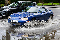 © Licensed to London News Pictures. 17/10/2019. London, UK. A car drives through a flood on Tottenham High Road after heavy downpour in north London this afternoon. Photo credit: Dinendra Haria/LNP
