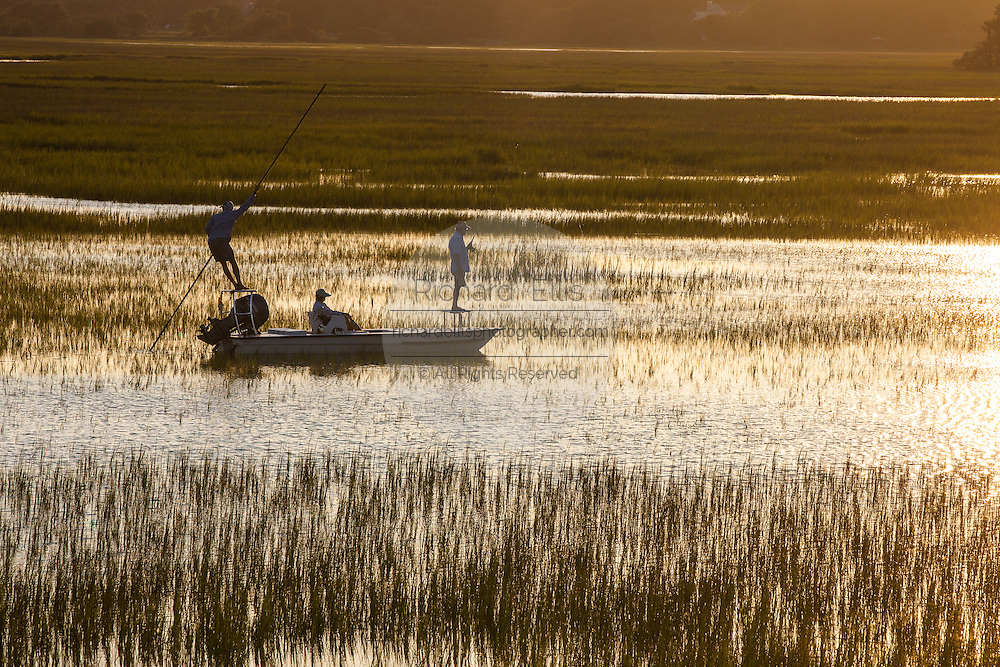 Fisherman pole their skill along the marsh near the Isle of Palms, SC.