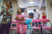"""31 MARCH 2013 - BANGKOK, THAILAND:     """"Nim"""" and her family during Easter services at the Thai Peace Foundation office in the Bangkapi section of Bangkok.     PHOTO BY JACK KURTZ"""