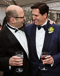 two men laughing at a wedding