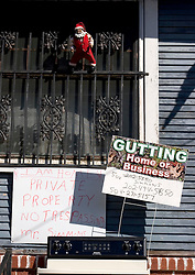 21December 05.  New Orleans, Louisiana. Post Katrina aftermath.<br /> New Orleans Christmas decorations. A santa claus sits atop window guards at a house in Uptown New Orleans.<br /> Photo; ©Charlie Varley/varleypix.com