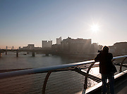 A tourist photographing the River Thames and Tower Bridge in London, UK