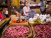 03 AUGUST 2017 - SUKAWATI, BALI, INDONESIA: A vender in the market in Sukawati. Bali's local markets are open on an every three day rotating schedule because venders travel from town to town. Before modern refrigeration and convenience stores became common place on Bali, markets were thriving community gatherings. Fewer people shop at markets now as more and more consumers go to convenience stores and more families have refrigerators.    PHOTO BY JACK KURTZ