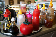Tray of condiments and sauces in eclectic shaped bottles in a cafe in London, England, United Kingdom. Included is the iconic tomato squeezy bottle.