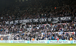Newcastle United fans holding up a banner during the game