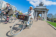 """Reaching Hyde Park Corner. The Tweed Run 2015 - it's 7th annual British public bicycle ride through London's historic streets, with a prerequisite that participants are dressed in their best tweed cycling attire. There are also plenty of handle bar moustaches, penny farthings and Union Jacks. """"Guests can expect a leisurely day cycling, stopping at some of London's most iconic landmarks to enjoy a spot of tea, a picnic in the park and finally a jolly good knees-up in a beautiful art-deco ballroom for the Tweed Run closing ceremony. Starting at Trafalgar Square, the cyclists then embarked on a 12 mile scenic ride through London, stopping at traditional spots."""