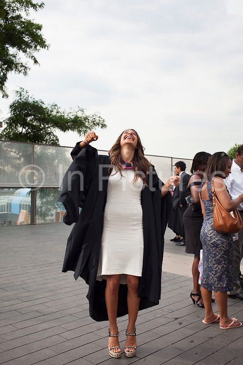 Graduates from UAL wearing cap and gown celebrate outside the Royal Festival Hall follwing their graduation ceremony. The students gather having their photos taken and throwing their mortar board hats into the air. University of the Arts London is a public research university located in London, UK specialised in art, design, fashion and media.