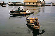 Small boats selling bread in informal housing wooden shacks built on timber logs known as the Floating City, Manaus, Brazil 1962