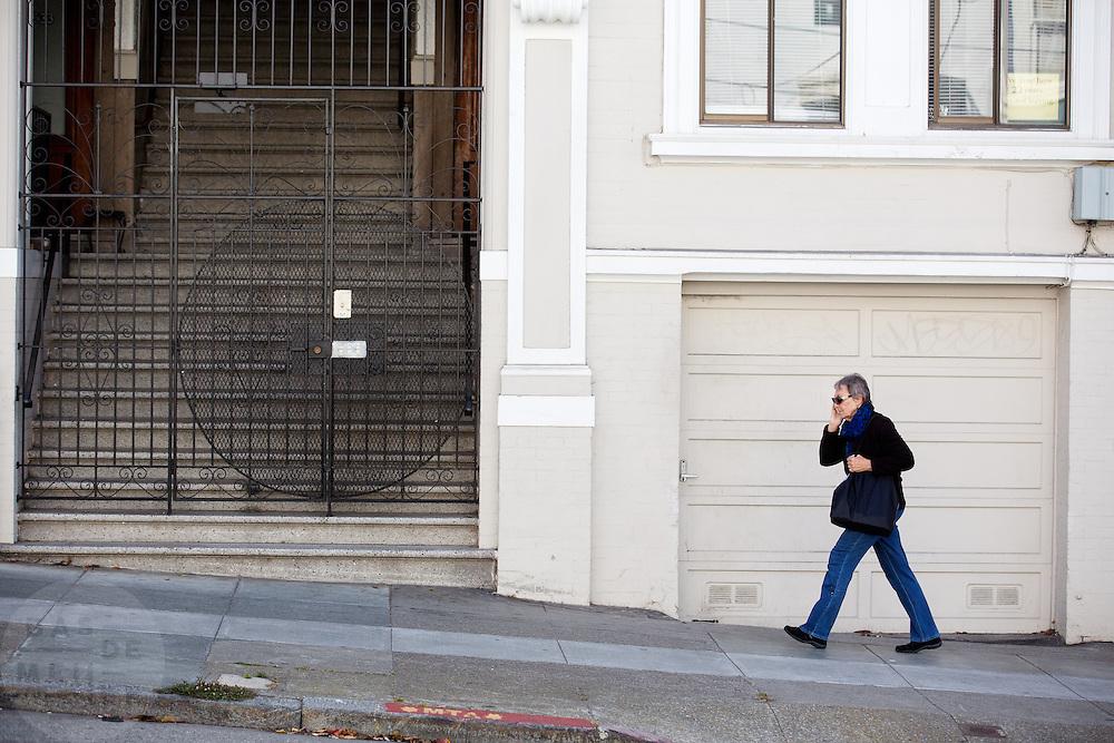 Een vrouw loopt bellend over een van de heuvels in San Francisco. De Amerikaanse stad San Francisco aan de westkust is een van de grootste steden in Amerika en kenmerkt zich door de steile heuvels in de stad.<br /> <br /> A woman walks a hill in San Francisco. The US city of San Francisco on the west coast is one of the largest cities in America and is characterized by the steep hills in the city.