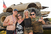 Cast members of the reality TV show Myrtle Beach Manor pose in front of a monster truck at the 2015 National Red Neck Championships May 2, 2015 in Augusta, Georgia. Hundreds of people joined in a day of country sport and activities.