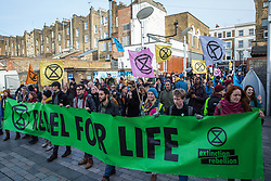 London, UK. 9th February, 2019. Activists from Extinction Rebellion march into Gillett Square in Dalston as part of a 'Saturday street party' intended as a means of engagement around climate change and environmental issues with the local community.