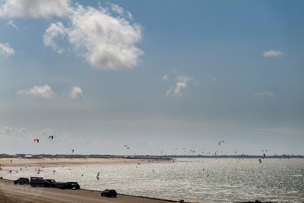 Kitesurfers en windsurfers bij de Brouwersdam. De dam is het zevende bouwwerk van de Deltawerken en vormt de afscheiding van het Grevelingenmeer met de Noordzee. Halverwege de dam vindt veel recreatie plaats met kitesurfers aan de zeekant en vakantieparken met jachthavens aan de kant van het meer.<br /> <br /> Kitesurfers and wind surfers at the Brouwersdam. The dam is the seventh structure of the Delta Works and forms the separation of the Grevelingenmeer with the North Sea. Halfway through the dam there is a lot of recreation with kite surfers on the sea side and holiday parks with marinas on the side of the lake.