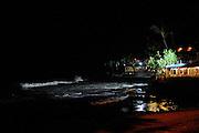 Restaurants and shops and breaking surf at night. Kailua-Kona, Big Island, Hawaii