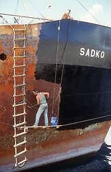 Two men painting ship in Las Palmas harbour; Gran Canaria; Canary Islands Spain,