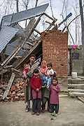 (L-R) Shugufta's husband carrying their son Zainab, 10 months, Igra, 8, Shugufta, 29, carrying Azra, 5, and Muzamil, 6, as the family poses for a portrait in front of their collapsed house in Narbal village, Jammu and Kashmir, India, on 24th March 2015. When the floods hit in the middle of the night, Shugufta and her family had to walk 5 miles to find shelter. Save the Children supported the family with shelter kits, blankets, hygiene items, food and tarpaulin, which they have used to build a temporary shelter next to their crumbled home. Photo by Suzanne Lee for Save the Children