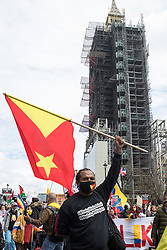 London, UK. 22nd May, 2021. An activist holding a Tigray flag takes part in the International Bloc highlighting human rights abuses taking place in Colombia and Tigray as well as Palestine and Israel on the National Demonstration for Palestine. The demonstration was organised by pro-Palestinian solidarity groups in protest against Israel's recent attacks on Gaza, its incursions at the Al-Aqsa mosque and its attempts to forcibly displace Palestinian families from the Sheikh Jarrah neighbourhood of East Jerusalem.