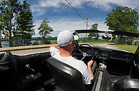 Denis Finnerty of Finn's Garage driving down Waukewan Street in a 1965 Ford Mustang convertible.  (Karen Bobotas/for the Laconia Daily Sun)