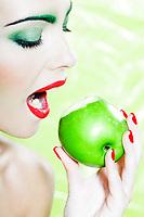 beautiful caucasian woman portrait eat an apple studio on green background