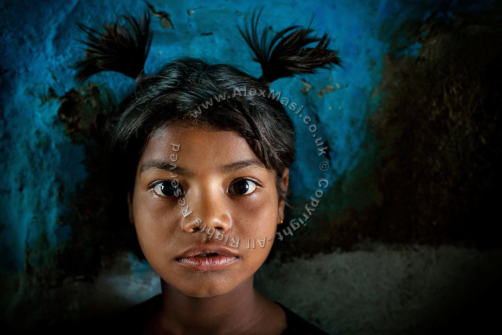 Poonam, 9, is standing inside her old home, where she lived until June 2011, on the day Alex and the young girl have met again, after his image of her, sitting under the heavy rain, was granted 5000 US dollars by 'The Photographers Giving Back Awards', in Sweden, destined towards her wellbeing, in Oriya Basti, one of the water-contaminated colonies in Bhopal, central India, near the abandoned Union Carbide (now DOW Chemical) industrial complex, site of the infamous '1984 Gas Disaster'.