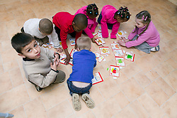 Multiracial group of children doing a giant jigsaw together on the floor,