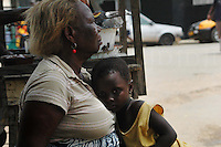 Ghana, Accra, 2007. Grandmother provides a refuge for this young child on an Accra back street.