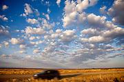 SUV drives under the clouds at dawn near Keetmanshoop, Namibia