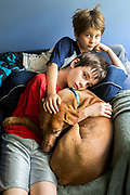 Children snuggle with a dog.