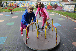 Two girls on roundabout in urban park