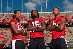 """01 October 2010: North Carolina State Wolfpack wide receivers Owen Spencer (13), Darrell Davis (15) and Jarvis Williams (5) with mascot """"Tuffy"""" at Carter-Finley Stadium in Raleigh, NC."""