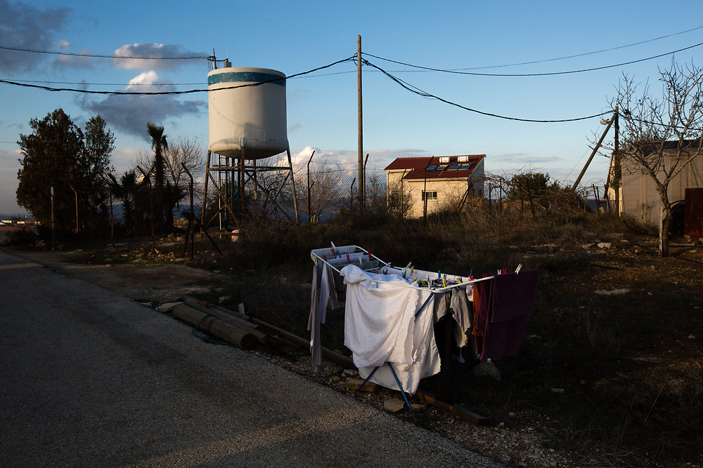 Laundry hangs to dry in front of a water tower, during sunset at the West Bank Jewish settlement of Eli, located south of the Palestinian West Bank town of Nablus, on January 1, 2017.