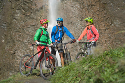 Three mountain biker friends standing in front of waterfall, Zillertal, Tyrol, Austria