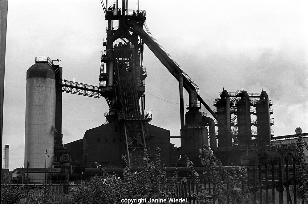 General view of the Elizabeth Blast Furnace plant at Bilston Steel works taken across the canal in 1978. Image shows the stove chimney,Cowper Stoves, Elizabeth furnace and skip bridge, and the gas cleaning plant. The blast furnace was mothballed on 2 October 1977 and was currently not in use. West Midlands