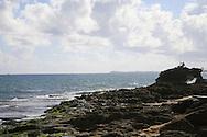 A lone fisherman on the rocks along the ocean in San Juan Puerto Rico